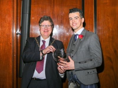 Apprentice of the Year Gareth Owen receives an engraved rose bowl from Master of the Glass Sellers Leigh Baildham