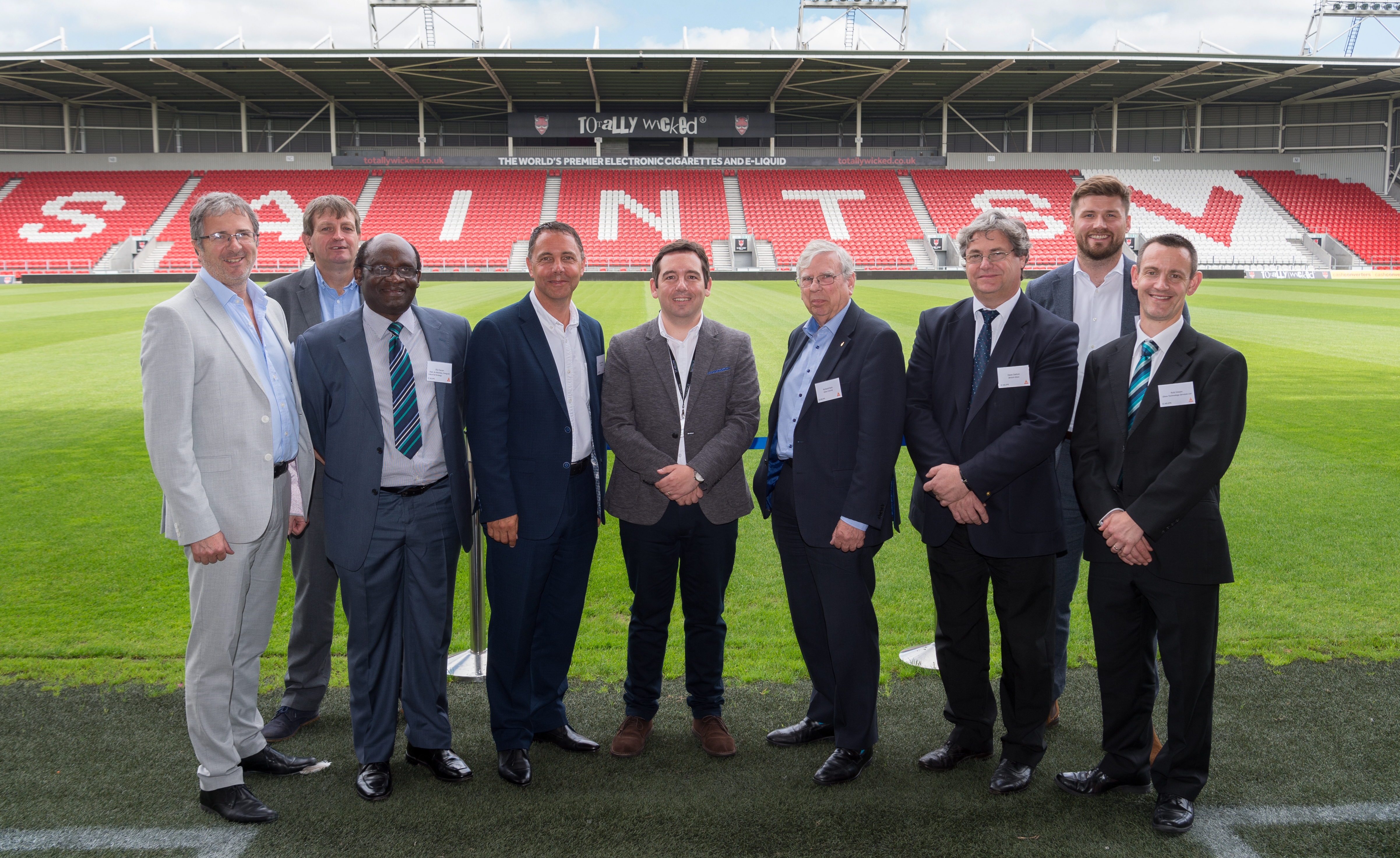 British Glass CEO Dave Dalton and Glass Technology Servcies' Rob Ireson pose on the Totally Wicked Stadium pitch alongside speakers from across the day including Cllr David Baines, leader of St Helens Council